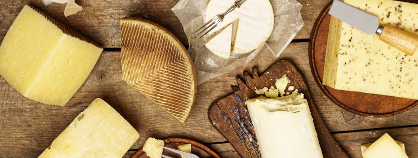 Various types of cheese on rustic background